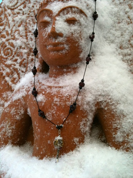 Garnet & Onyx Prayer Wheel Necklace on Snowy Buddha
